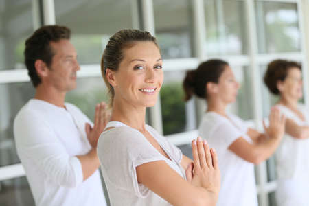 attending: Attractive blond woman attending yoga course with group