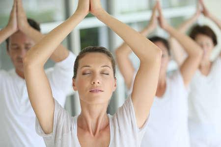 clases: Atractiva mujer rubia asistir curso de yoga con el grupo