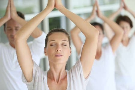 Attractive blond woman attending yoga course with group photo