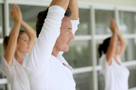 whiteness: Mature man amongst group doing yoga exercises Stock Photo