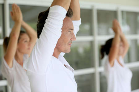 Mature man amongst group doing yoga exercises Stockfoto