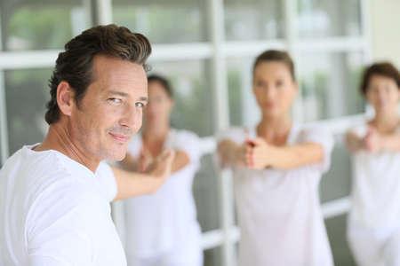 amongst: Mature man amongst group doing yoga exercises Stock Photo