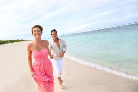 Romantický pár běží na písečné pláži