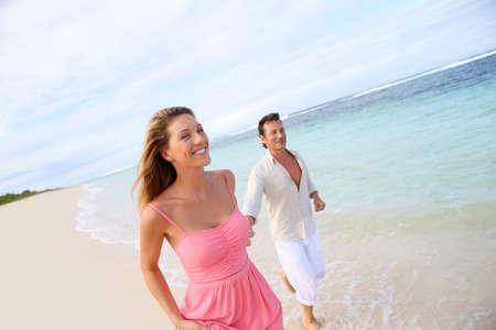 Romantic couple running on a sandy beach photo