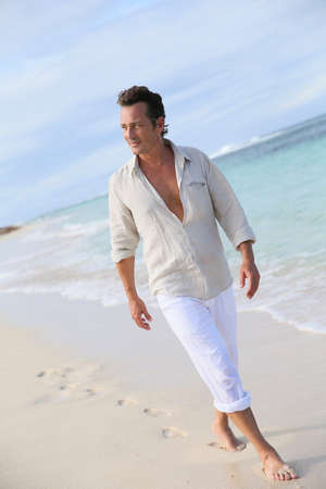 40 years old man: Handsome 40-year-old man walking on beach