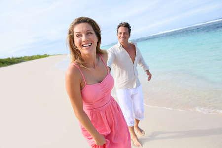 Cheerful couple running on a sandy beach photo