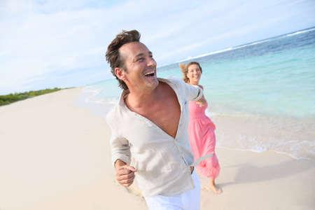 Couple having fun running on a caribbean beach photo