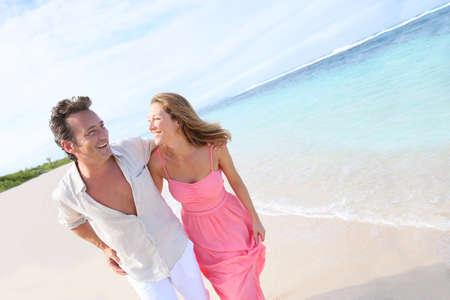 couple having fun: Couple having fun running on a caribbean beach