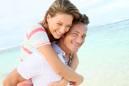 romantic couple: Man giving piggyback ride to girlfriend at the beach Stock Photo