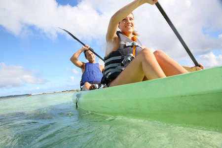 Couple canoeing in transparent caribbean sea Stock Photo