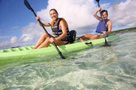 Couple canoeing in lagoon of West French indies Stock Photo