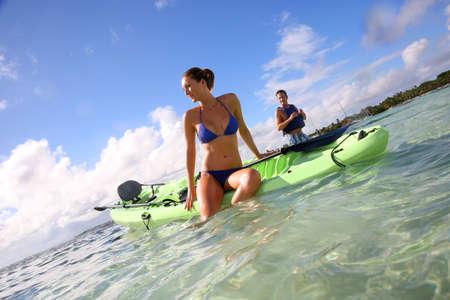 ocean kayak: Hermosa mujer con bikini posando sitted en canoa