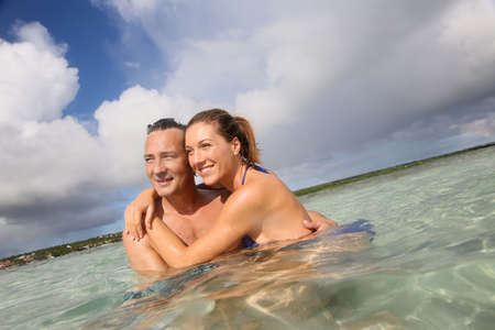 40s adult: Cheerful middle-aged couple embracing in the sea Stock Photo