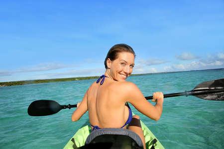 kayaker: Back view of beautiful woman paddling in canoe