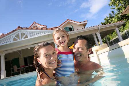 abrazar familia: Familia que juega en la piscina de la villa privada