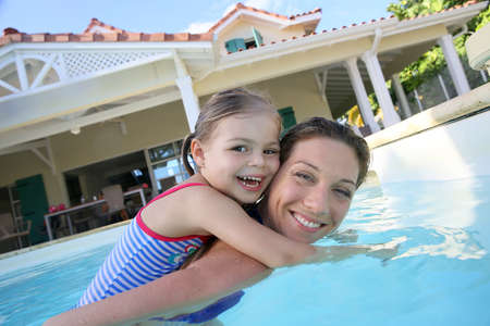 Mother and daughter playing together in pool photo