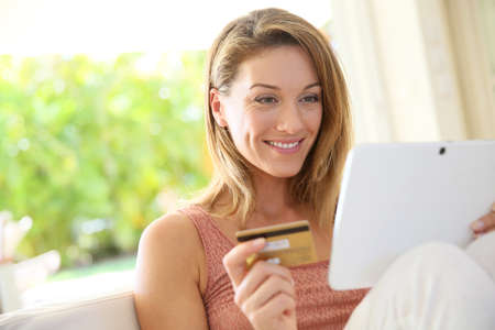 secured payment: Portrait of woman shopping on internet with tablet