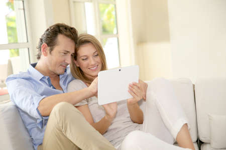 websurfing: Couple in sofa websurfing on internet Stock Photo