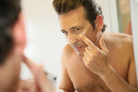 Middle-aged man in bathroom applying facial lotion photo