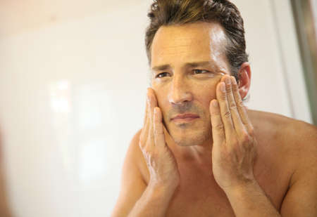 treatments: Middle-aged man in bathroom applying facial lotion