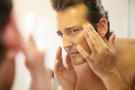 beauty skin: Middle-aged man in bathroom applying facial lotion