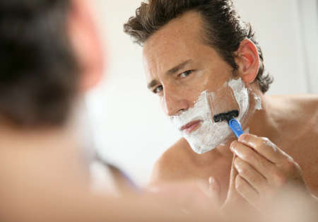 mirror face: Mature handsome man shaving in front of mirror