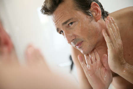 shaving cream: Handsome man rinsing face after shaving