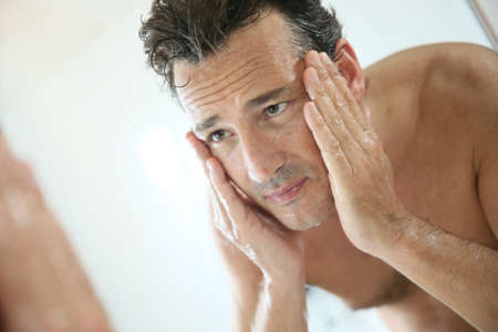 treatments: Handsome man rinsing face after shaving