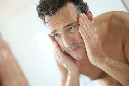 man face: Knappe man spoelen gezicht na het scheren