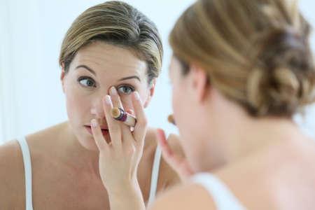concealer: Beautiful blond woman applying concealer around eyes