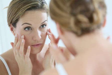 mujer maquillandose: Mujer de mediana edad de aplicar la crema anti-envejecimiento Foto de archivo