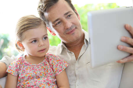 Man playing with little girl on digital tablet photo