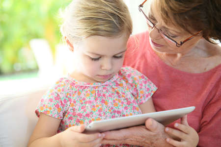 4-year-old girl with grandma playing on digital tablet photo