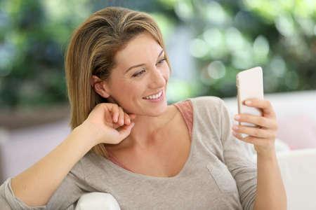 魅力的な中年女性はスマート フォンとメッセージング