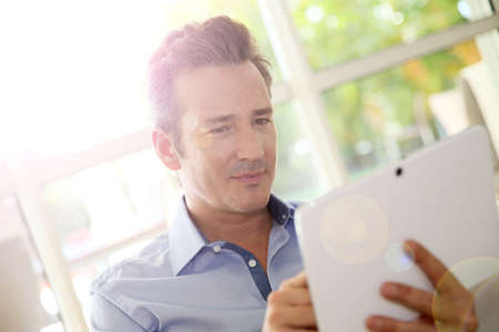 Portrait of middle-aged man at home using tablet photo