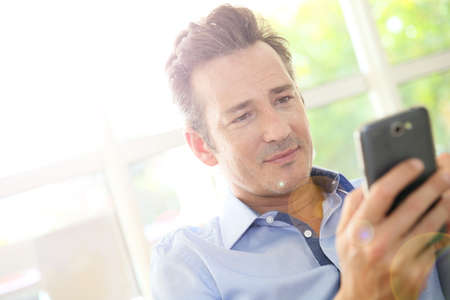 mature adult men: Portrait of middle-aged man using smartphone Stock Photo