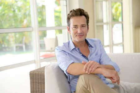 Portrait of single middle-aged man sitting in sofa Standard-Bild