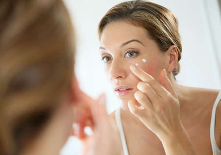 woman looking: Middle-aged woman applying anti-aging cream