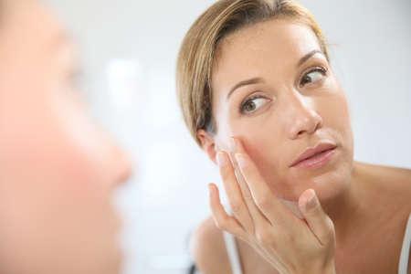 espejo: Mujer de mediana edad de aplicar la crema anti-envejecimiento Foto de archivo