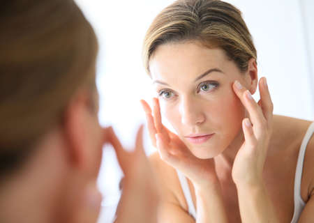 pretty face: Middle-aged woman applying anti-aging cream
