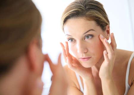 caras: Mujer de mediana edad de aplicar la crema anti-envejecimiento Foto de archivo
