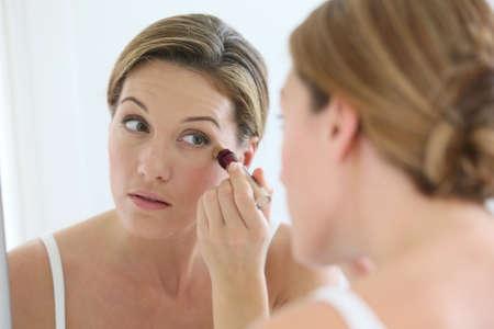 mujer maquillandose: Hermosa mujer rubia aplicar corrector alrededor de los ojos