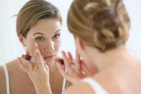 concealer: Bella donna bionda applicando correttore intorno agli occhi