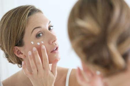 arrugas: Mujer de mediana edad de aplicar la crema anti-envejecimiento Foto de archivo