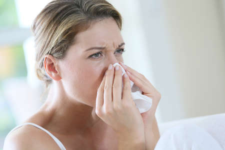 Portrait of womanwith allergy blowing her nose Stock Photo