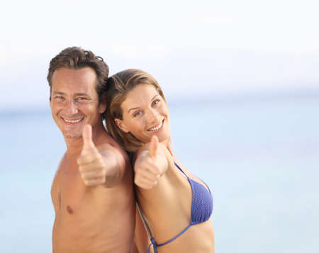 bikini couple: Middle-aged couple in swimsuit showing thumbs up