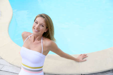beautycare: Attractive blond woman in swimsuit relaxing by pool