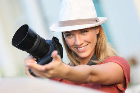 35 years old: Woman photographer taking picture of model outside