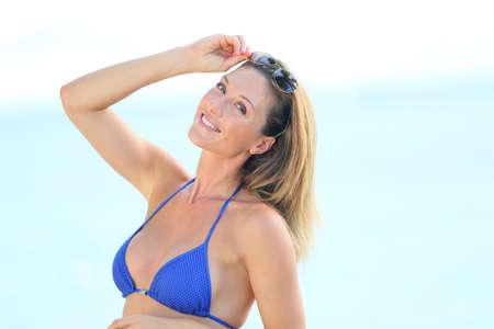 blue bikini: Blond woman in bikini with eyeglasses posing by the beach