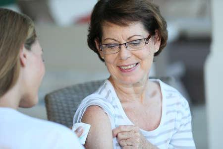 vacunaci�n: Mujer mayor que recibe la vacuna contra la gripe Foto de archivo